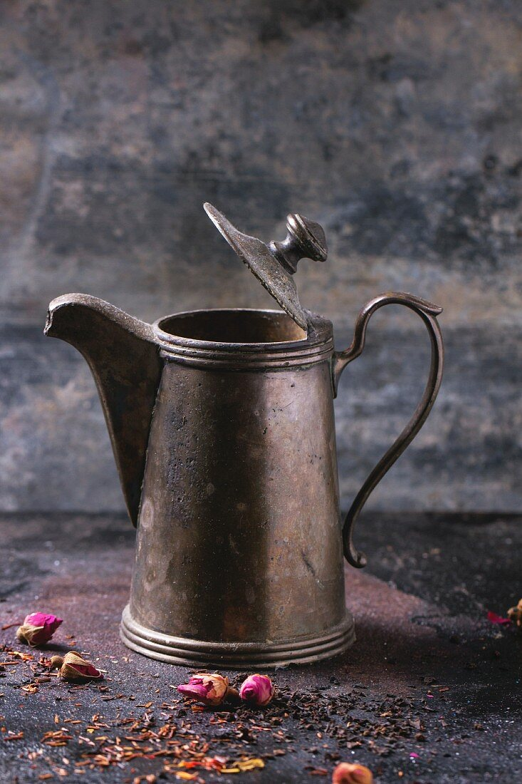 Open vintage teapot with dry tea and rose buds over black metal background