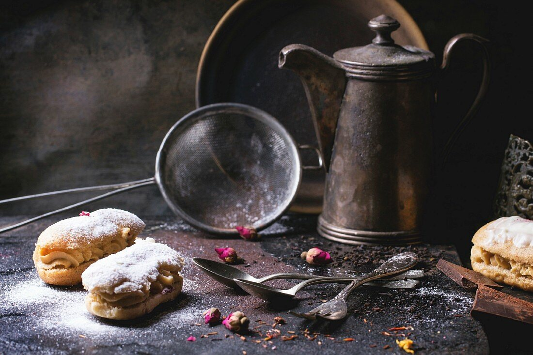 Tea drinking with eclairs and chopped chocolate, served with vintage teapot and cutlery over dark background