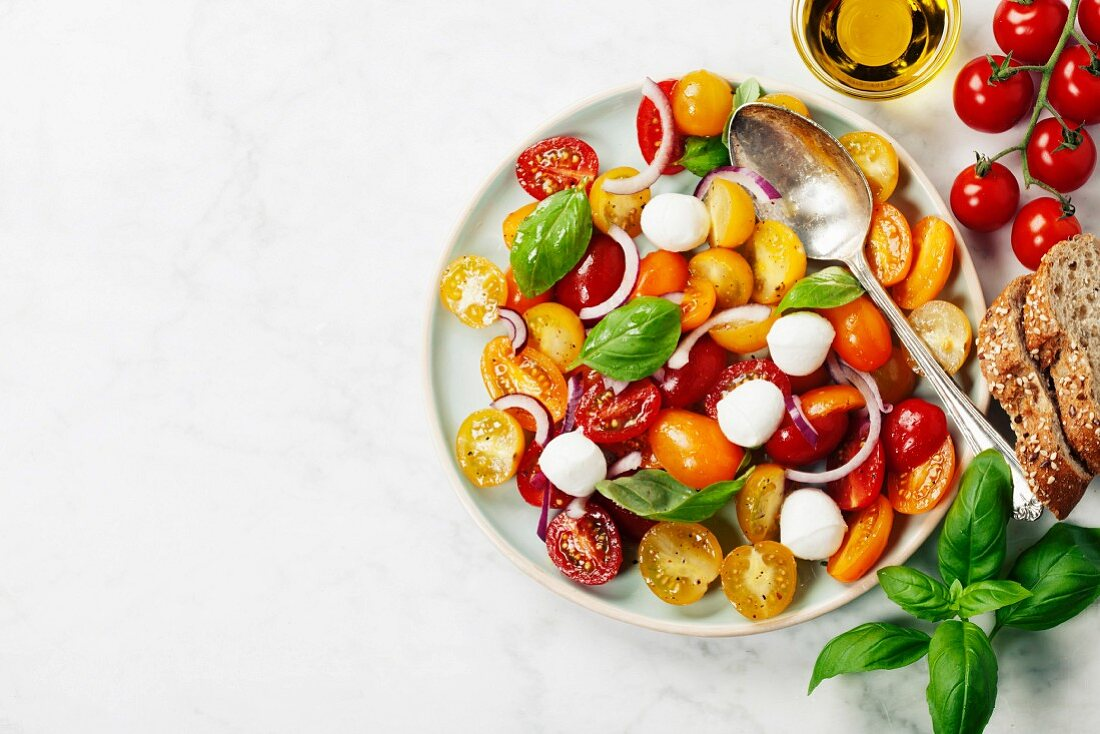 Blue plate of fresh and healthy Mediterranean salad with mozzarella cheese, tomatoes, red onion and basil leaves