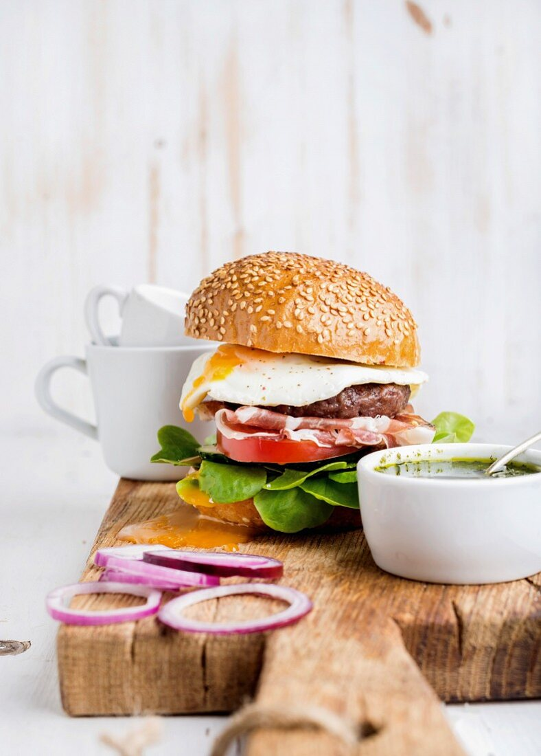 Fresh homemade burger with beef cutlet, egg, prosciutto and vegetables on wooden serving board