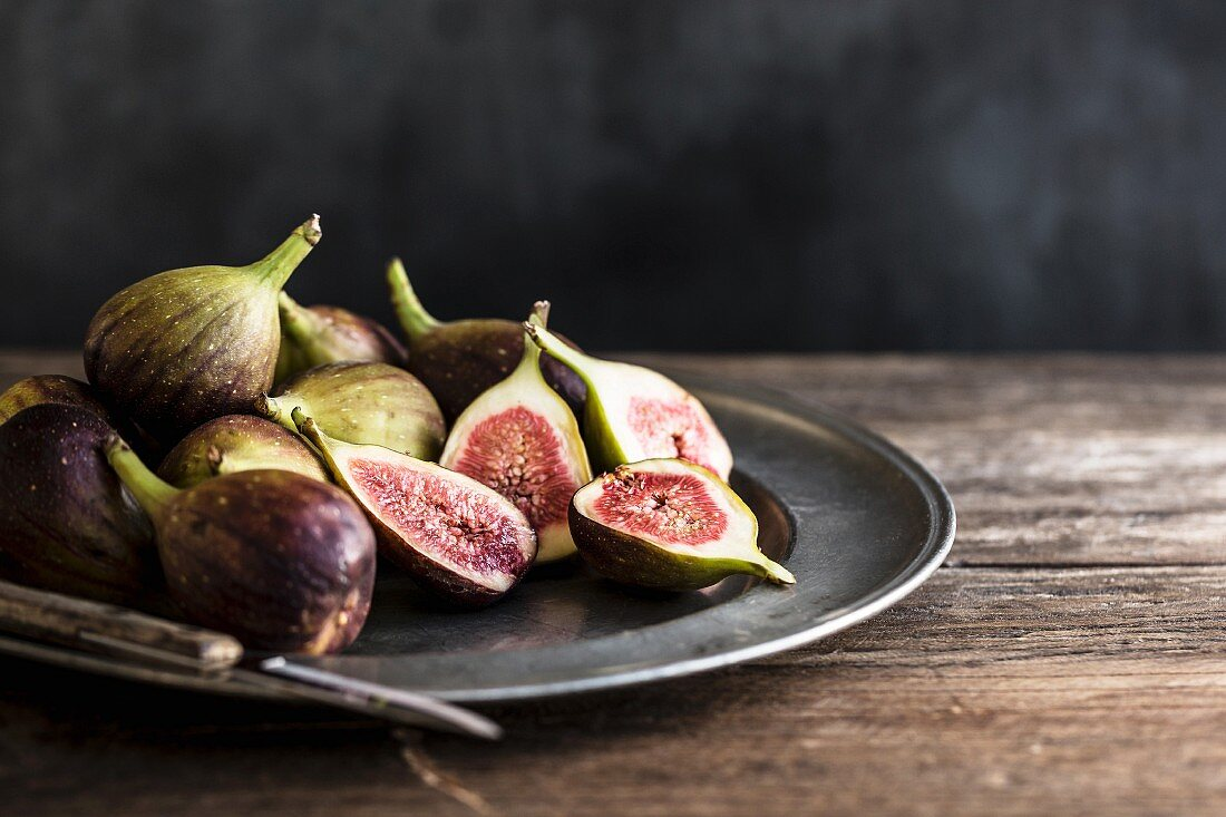 Whole and sliced figs on a metal plate with knife on a wooden table