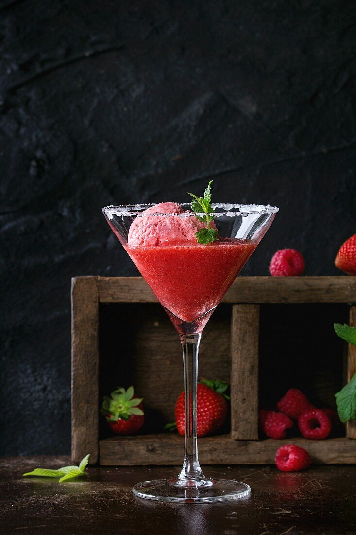 Sugared cocktail glass of strawberry dessert with sorbet, served on dark background with Strawberries