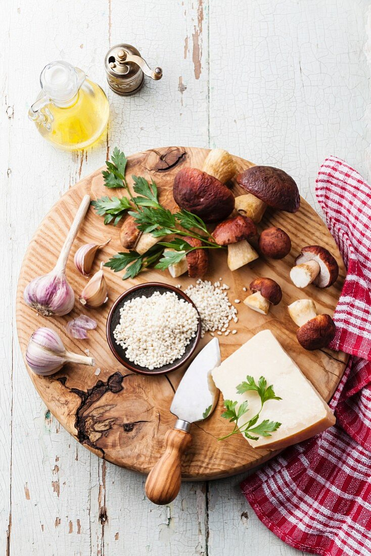 Ingredients for risotto with wild mushrooms on wooden background