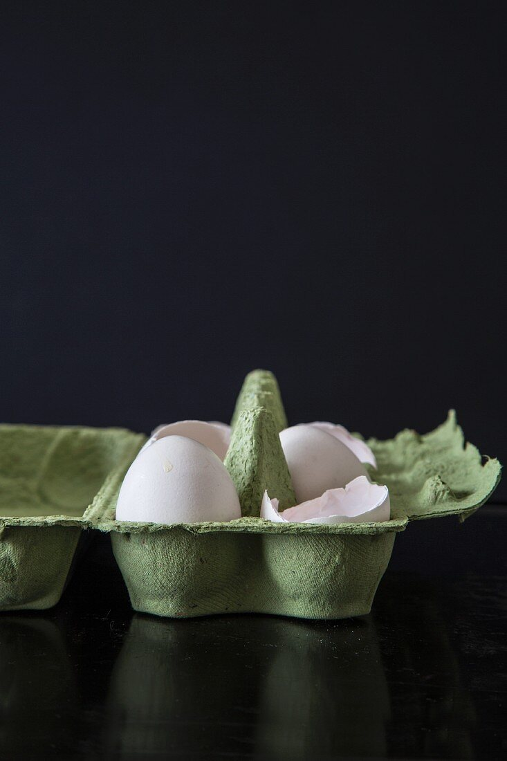 Eggs and eggshells in an egg carton