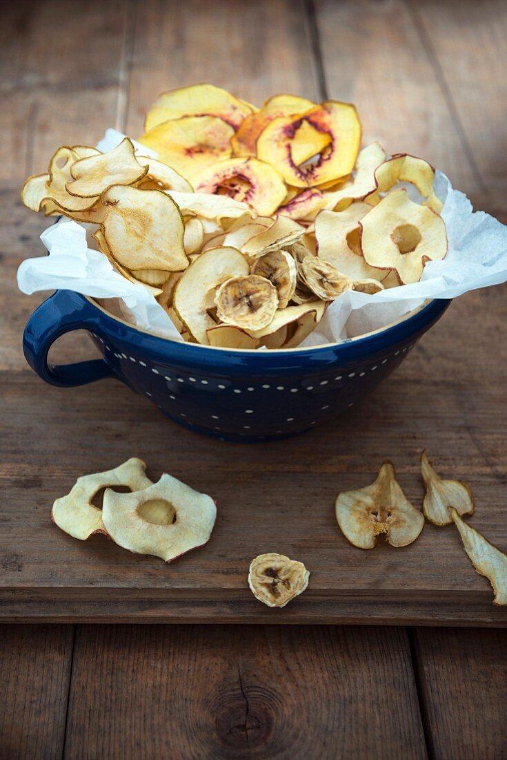 A bowl of banana, pear, apple and peach crisps