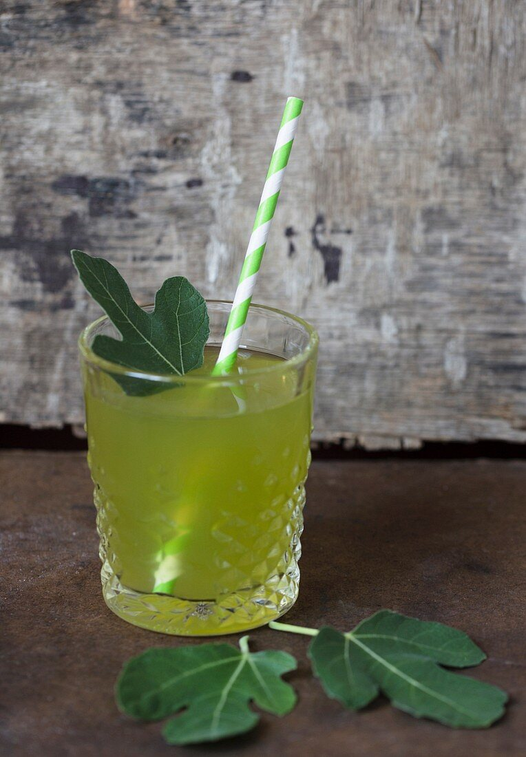 Fig leaves in a glass with a straw