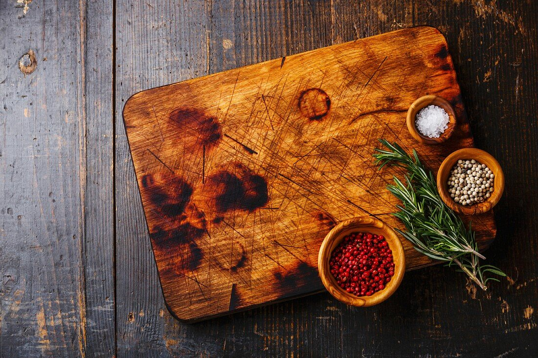 Chopping cutting kitchen board, salt, pepper and rosemary on dark wooden background