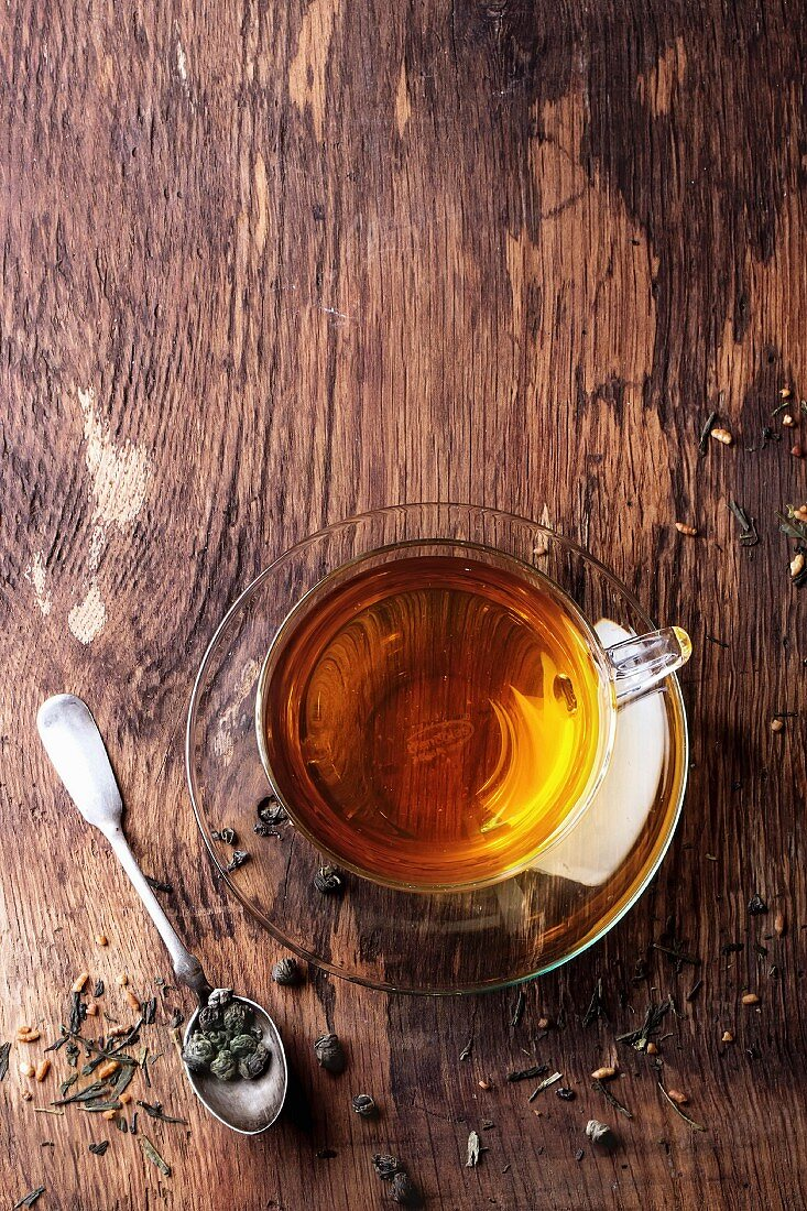Glass cup of hot tea with dry green tea leaves, vintage spoon and sugar on rustic wooden background