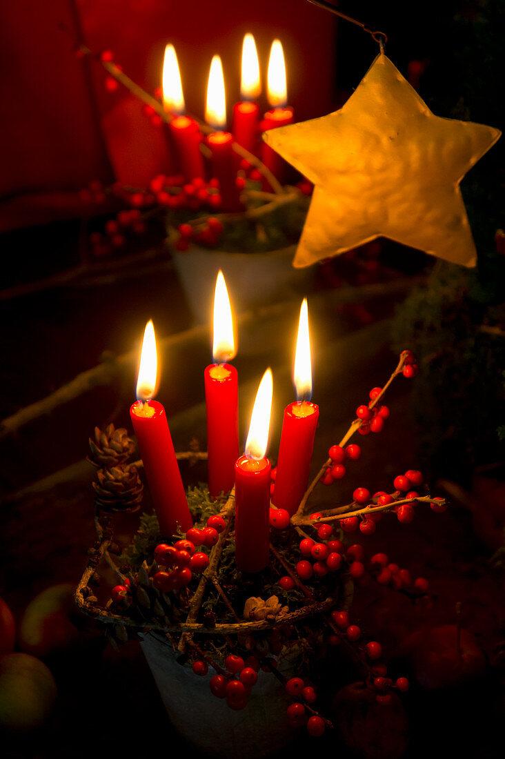 Christmas arrangement of terracotta pot, moss and four candles,