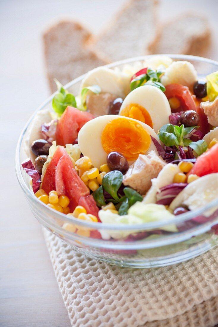 Salad bowl with tomatoes, corn, tuna, boiled egg, olives, mozzarella, radicchio and lambs lettuce