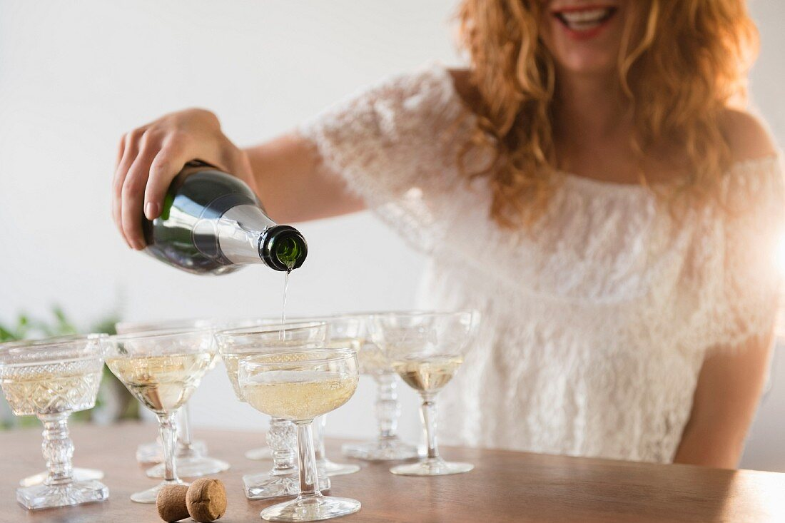 A smiling woman pouring champagne into champagne glasses