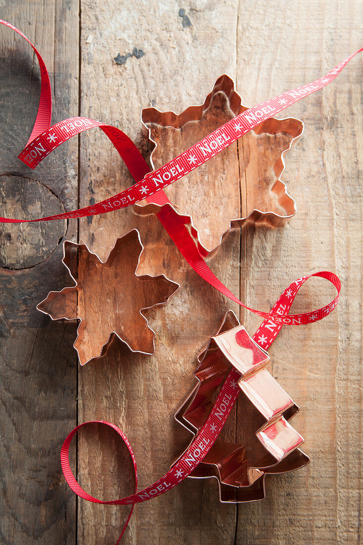 Snowflake and tree shape copper cookie cutters on a rustic wooden table with red Noel ribbon