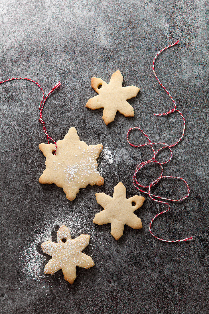Four snowflake shaped biscuits with a sprinkling of icing sugar in the process of being threaded with red and white bakers twine on a grey slate background