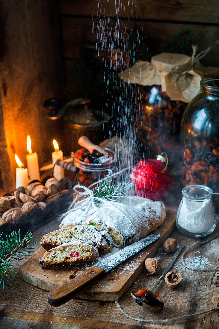 Icing sugar being dusted over a Christmas stollen