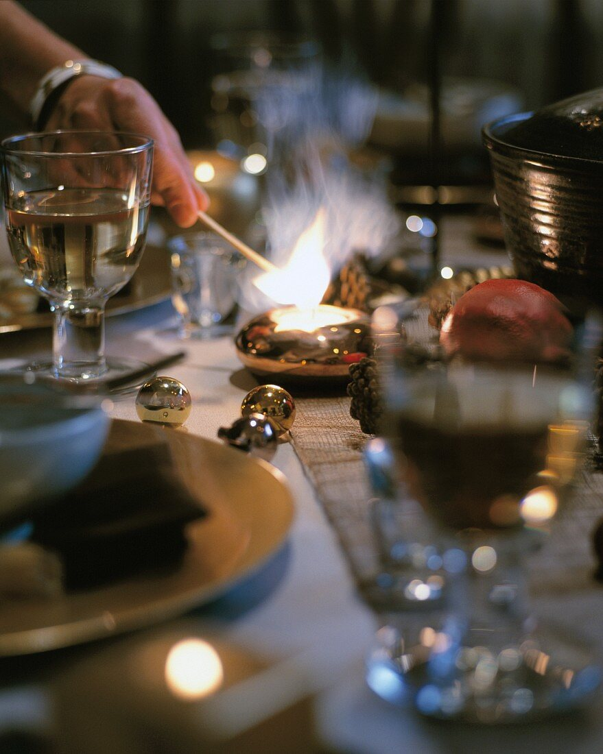 A candle being lit on a Christmas-themed dining table