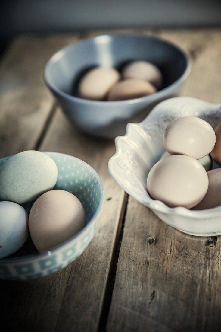 Various eggs in ceramic bowls