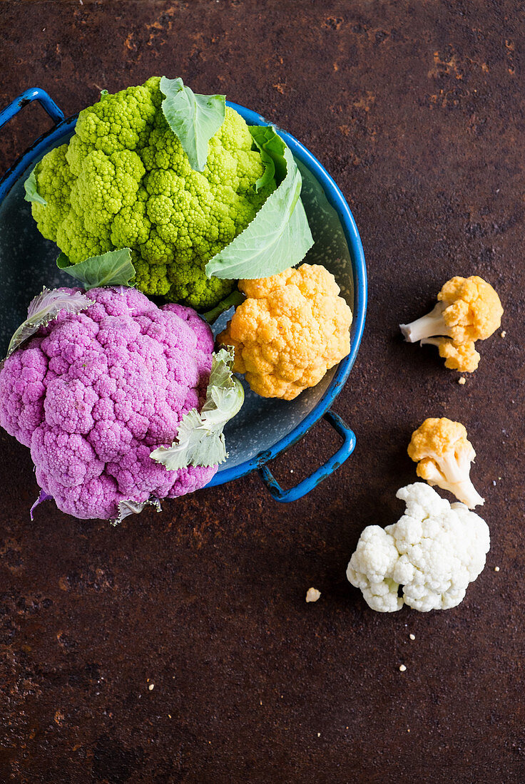 Various brightly coloured cauliflower florets in an enamel colander