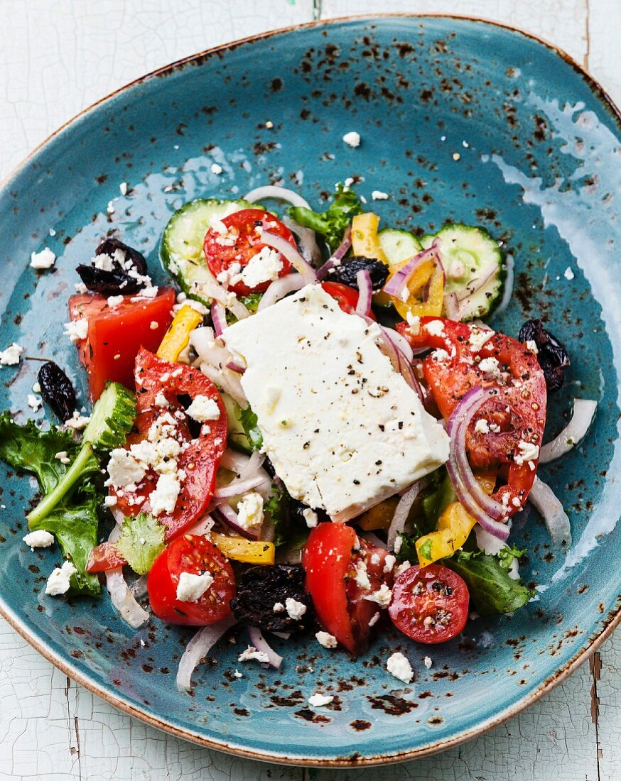 Greek salad with feta cheese and sun-dried olives on blue background