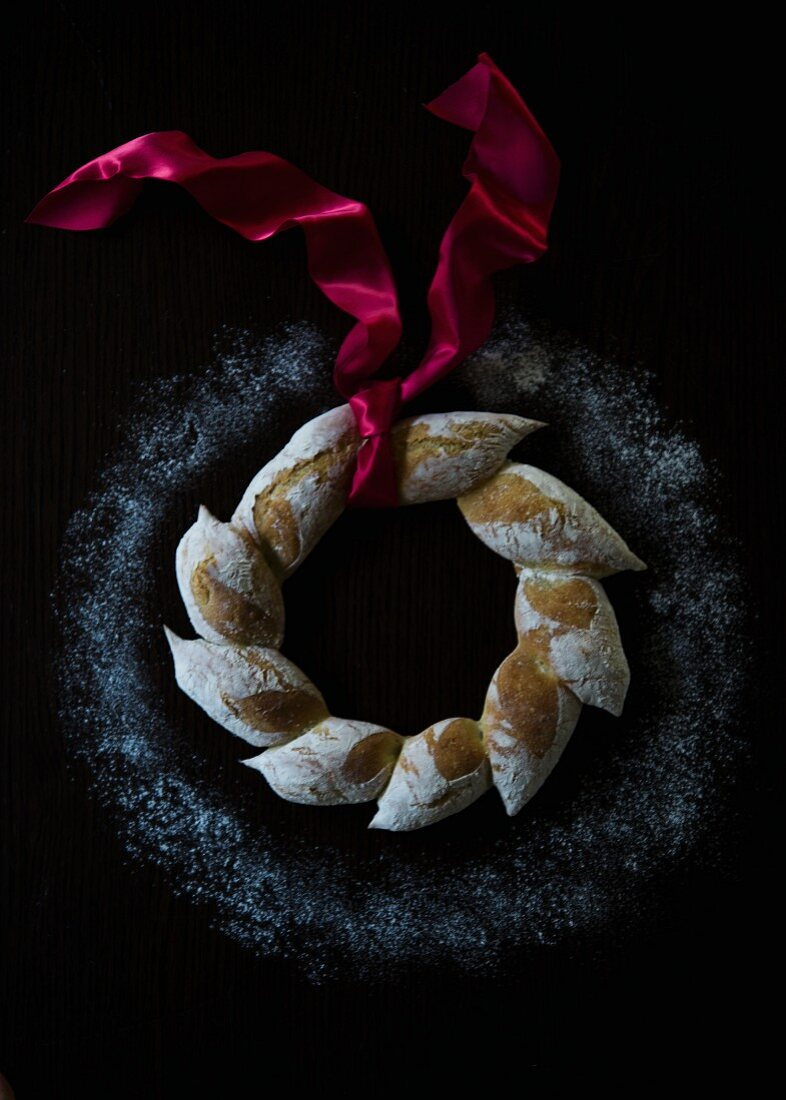An artisan bread wreath with a red satin ribbon