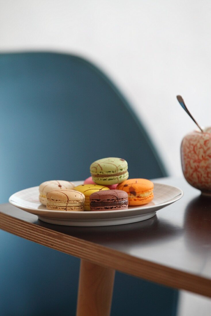 Plate of colourful macarons on table