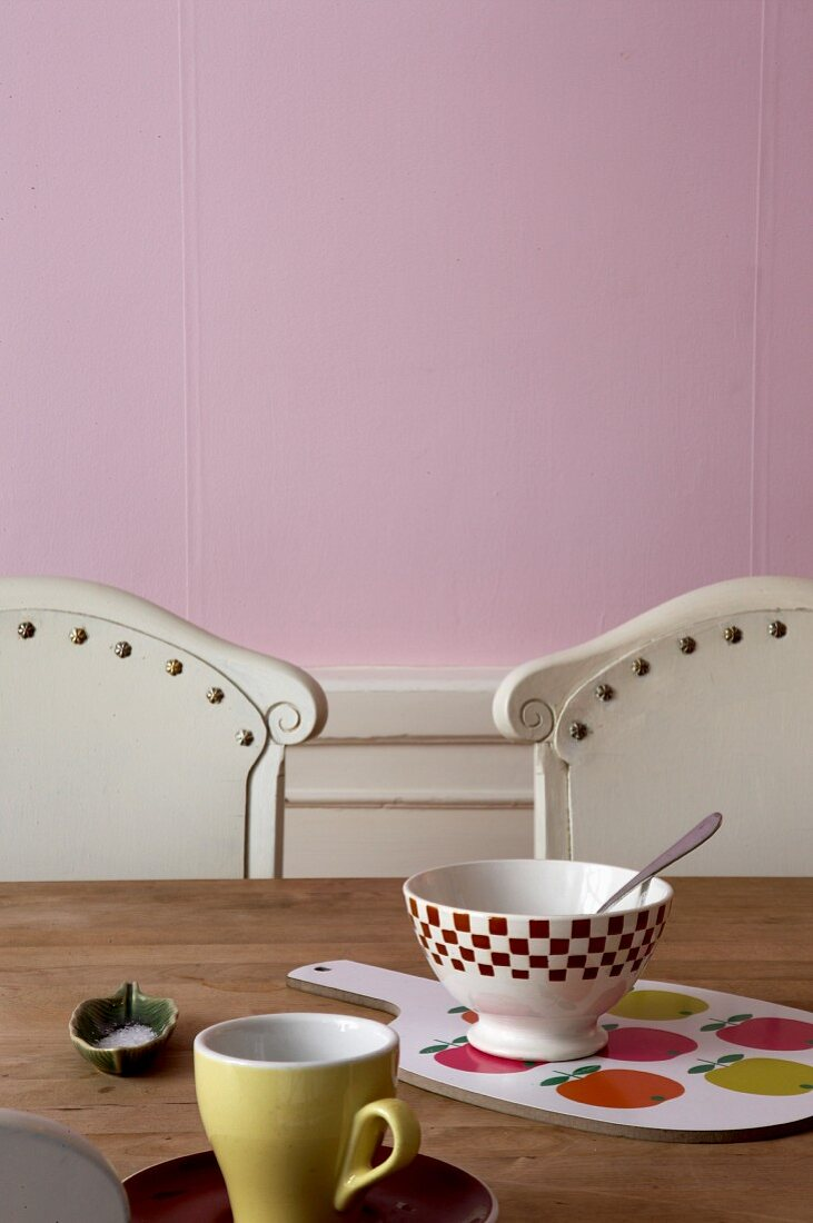 Bowls and chopping board on wooden table against pink wall