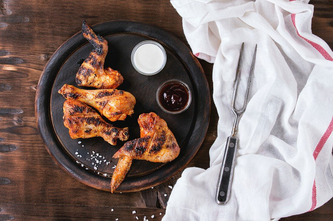 Grilled BBQ chicken meat wings and legs served on round wood chopping board with two sauces and salt