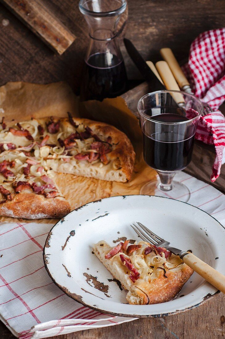 A slice cut out of a rustic pizza with bacon and onion