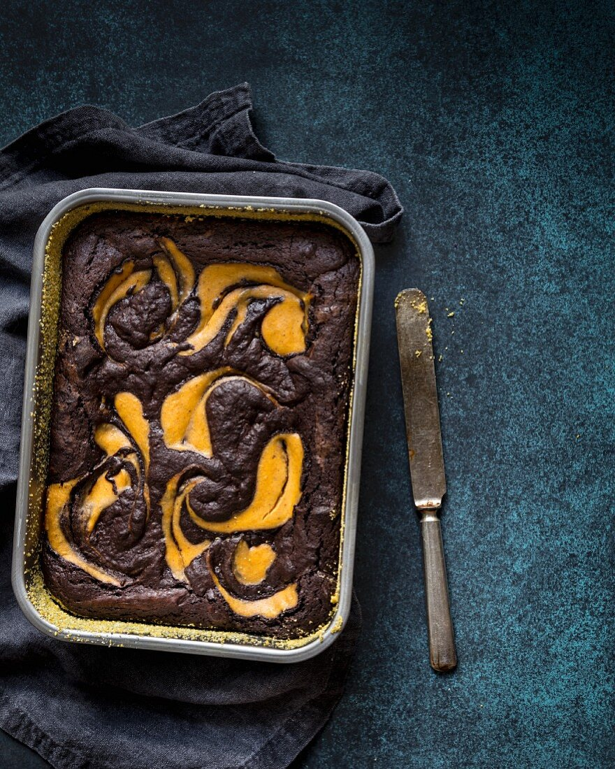 Gluten-free brownie and pumpkin cake in a baking tin