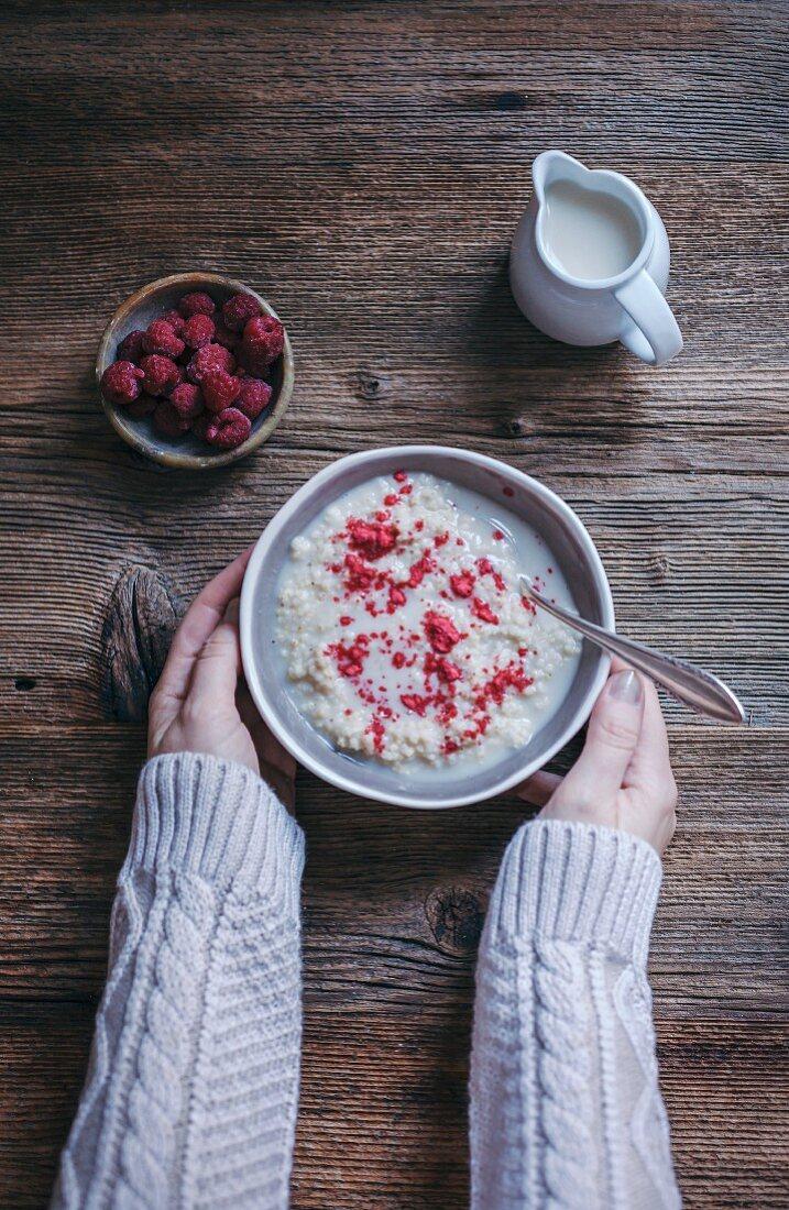 Woman eating millet porridge with raspberry powder