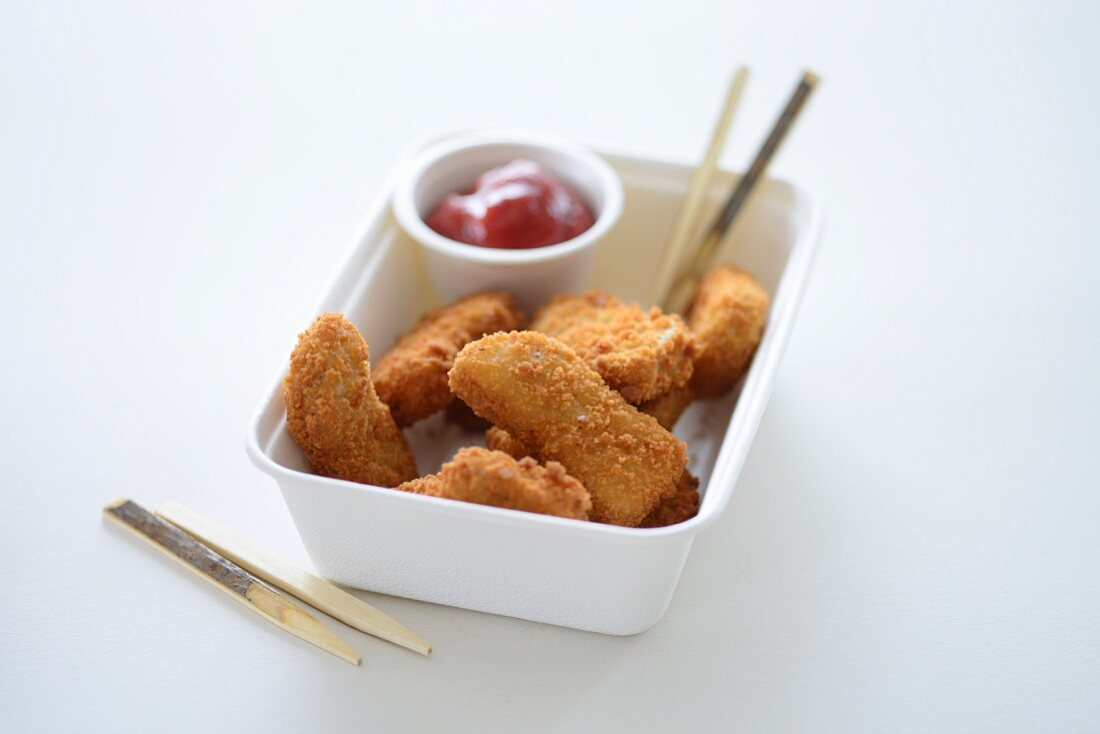 Chicken nuggets and ketchup in a takeaway carton