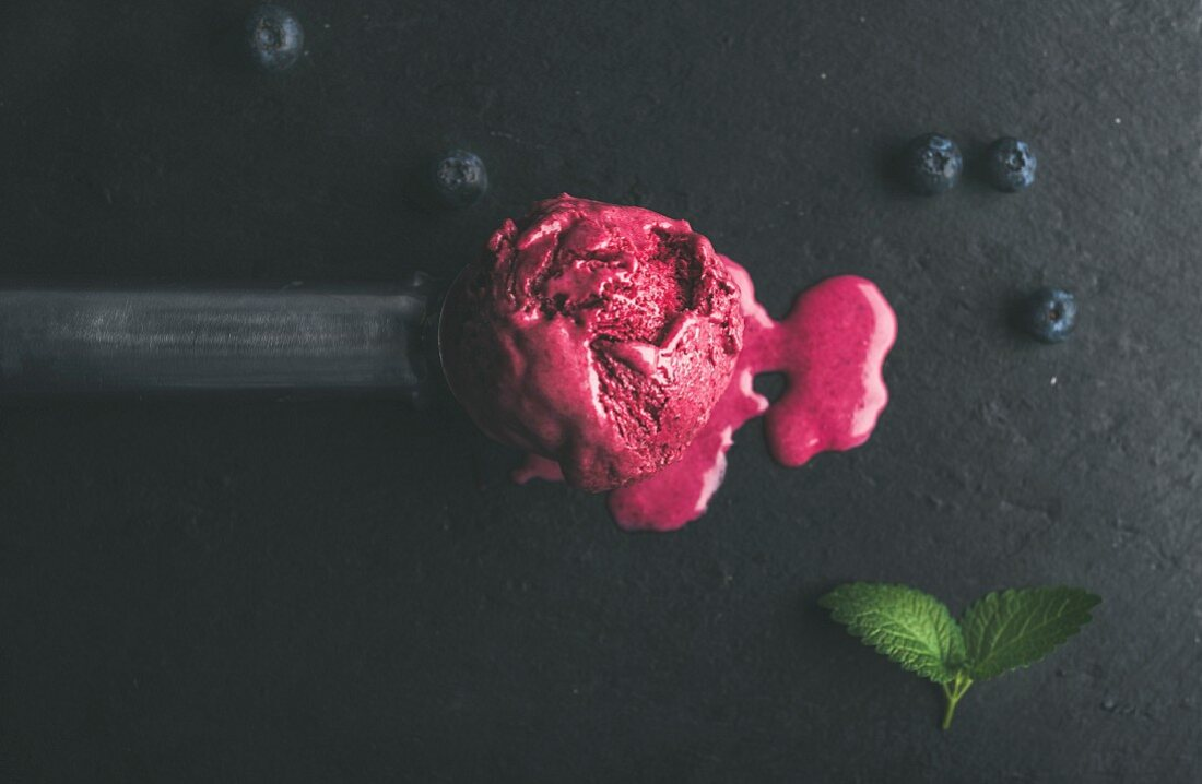 Melting scoop of blueberry ice-cream with mint leaves over black slate stone background