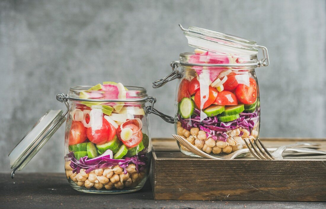 Vegetable and chickpea sprout vegan salad in glass jars, grey concrete wall background