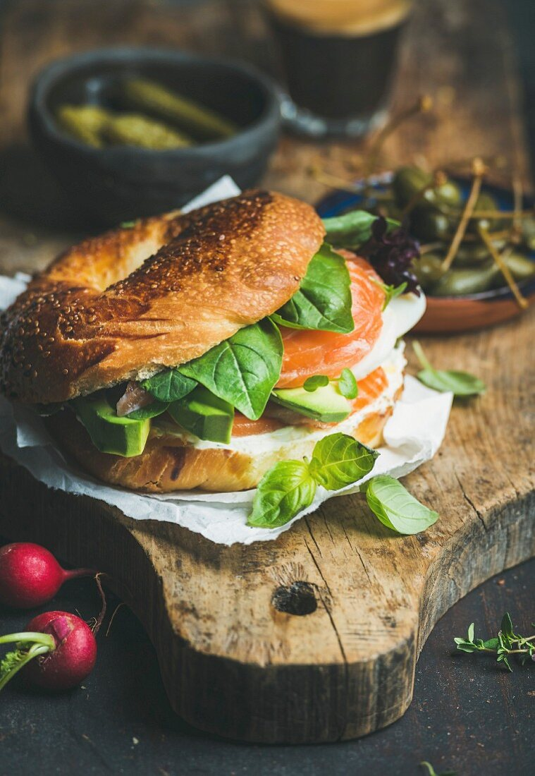 Breakfast with bagel with salmon, avocado, cream-cheese, basil and espresso coffee
