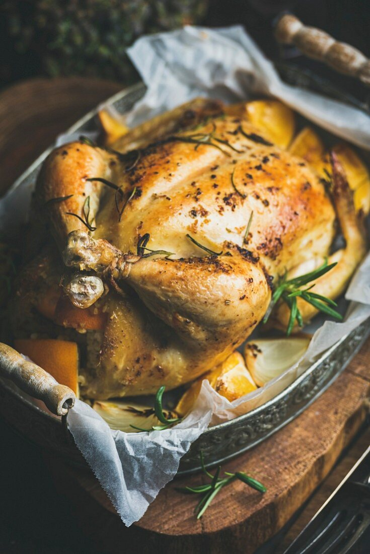 Christmas roasted whole chicken stuffed with oranges, bulgur and rosemary in vintage metal tray