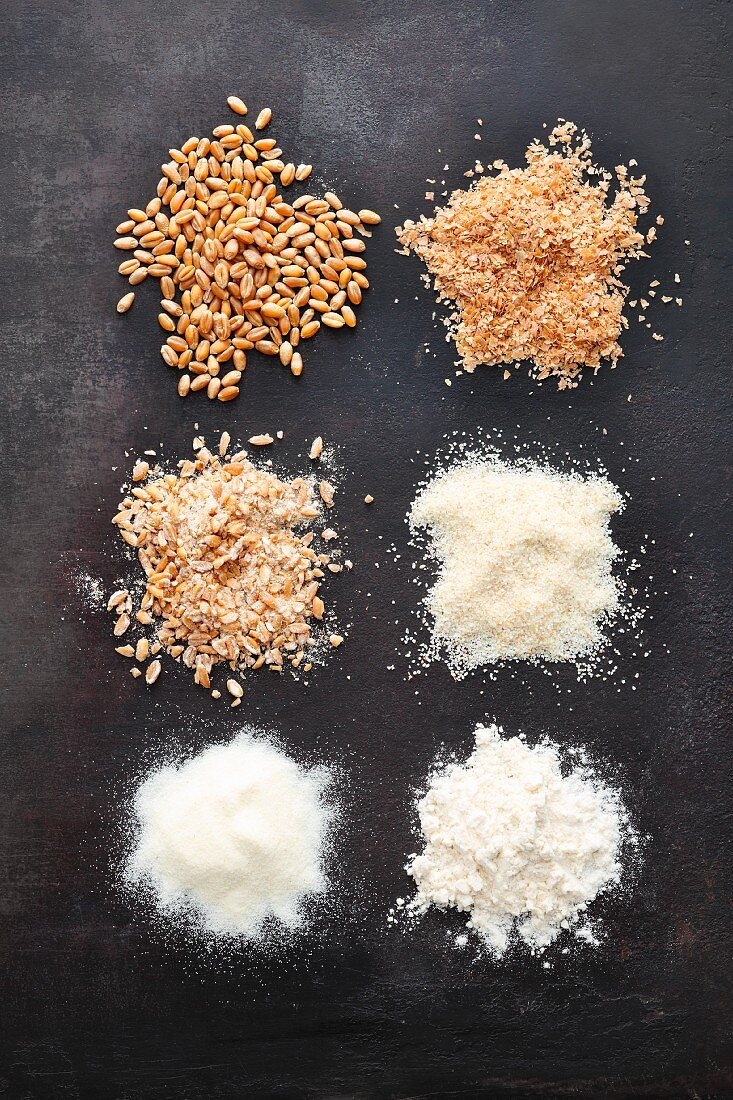 Cereal grains in different degrees of grinding: bran, coarsely ground meal, grit, coarse-grained flour and flour