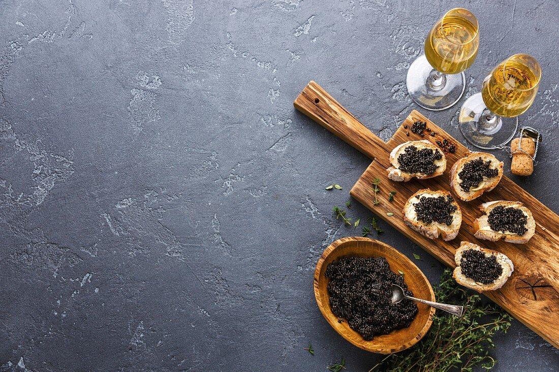 Sturgeon black caviar in wooden bowl, sandwiches and champagne on dark stone background