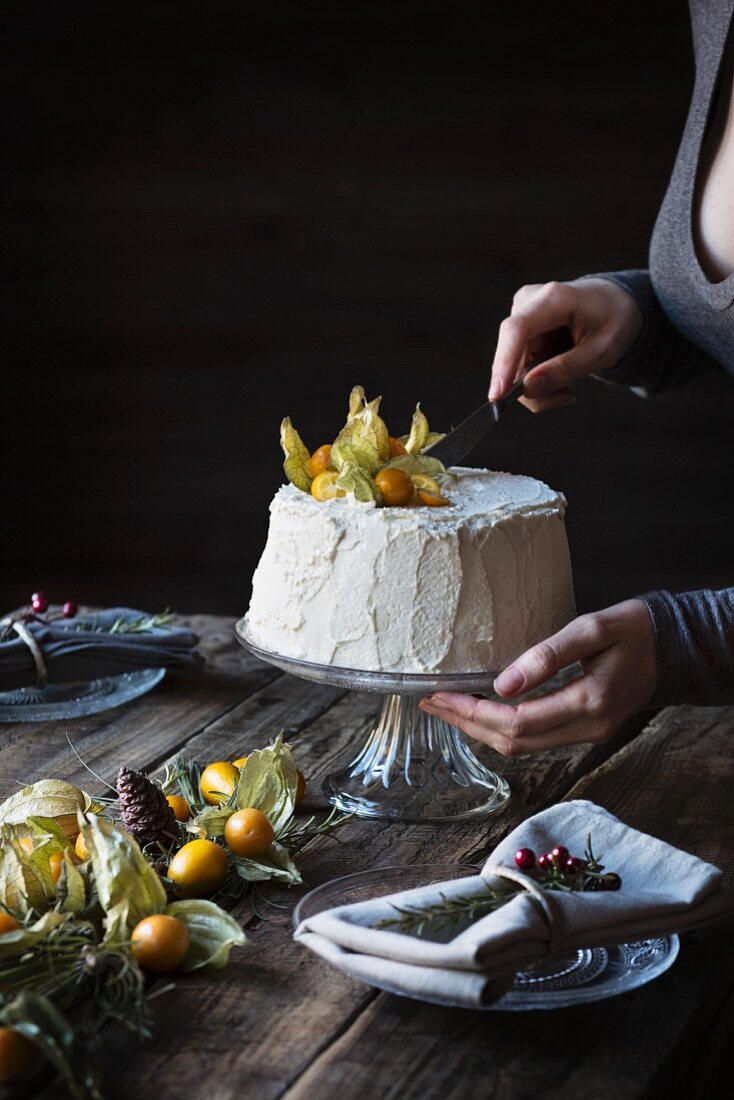 Woman cutting a chiffon cake on wooden table