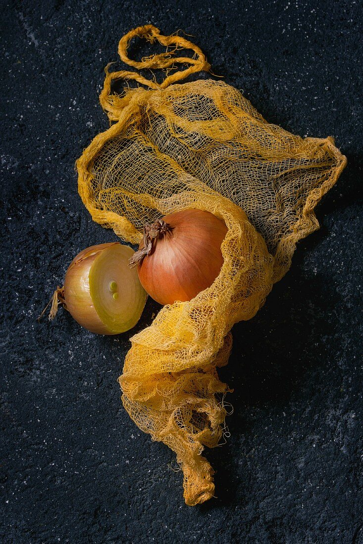 Whole and half of yellow onions in yellow rag over black stone background