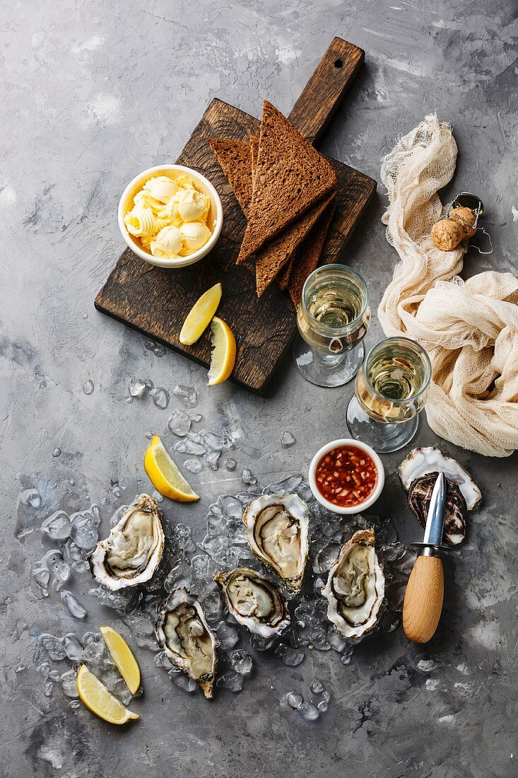 Open Oysters with bread and butter and champagne on gray concrete texture background