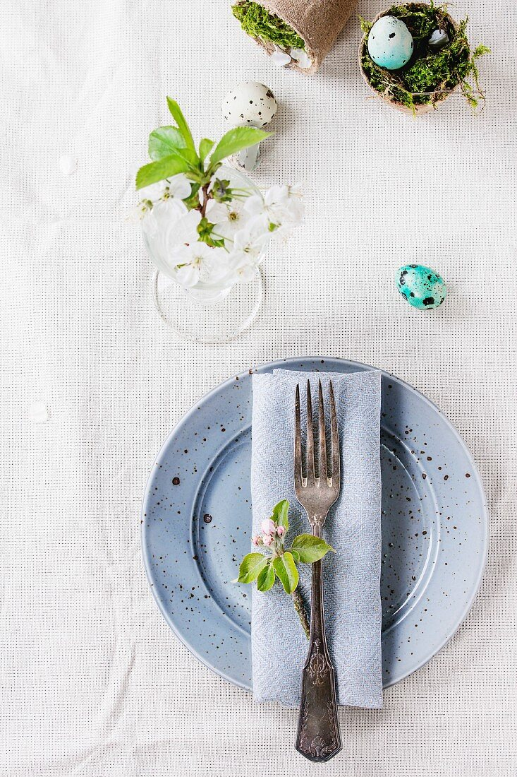 Colorful Easter quail eggs with spring cherry flowers, moss in garden pots, empty plates, vintage cutlery