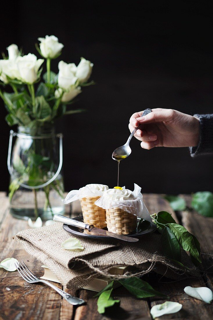 Hand of woman pouring oil on ricotta cheese