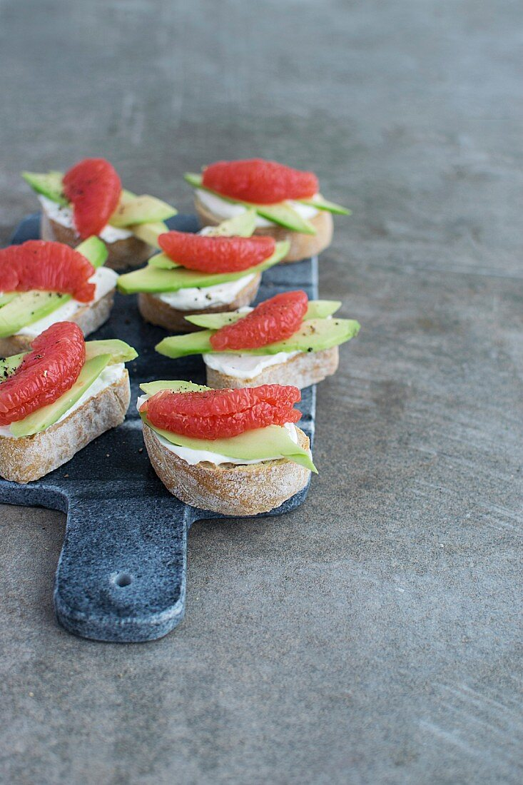 Crostini topped with chevre cheese, avocado and grapefruit