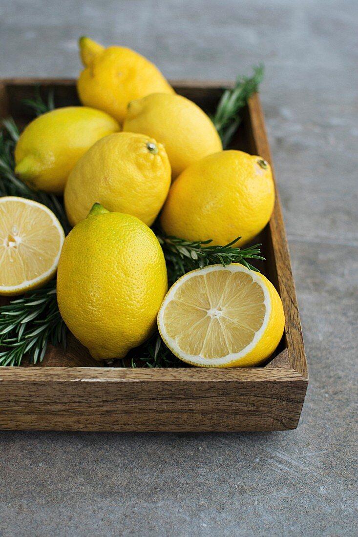Zitronen und Rosmarin auf Holztablett