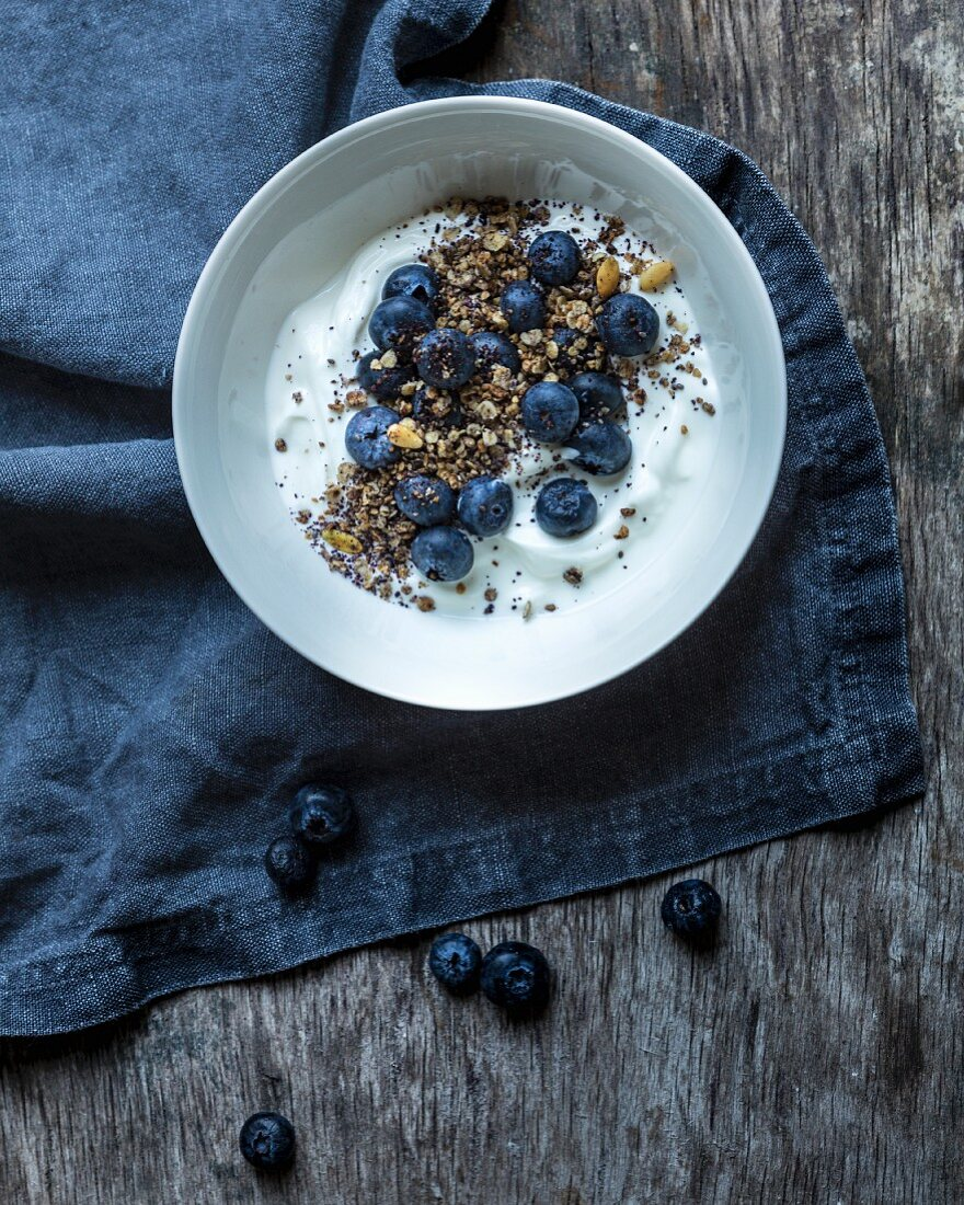 Yoghurt muesli with blueberries, blueberry powder, oat flakes and seeds