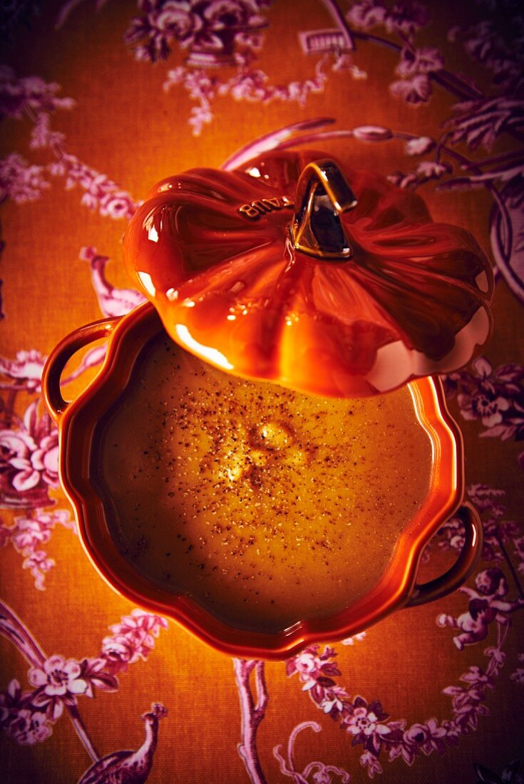 Butternut squash soup with chestnuts in an orange tureen (top view)