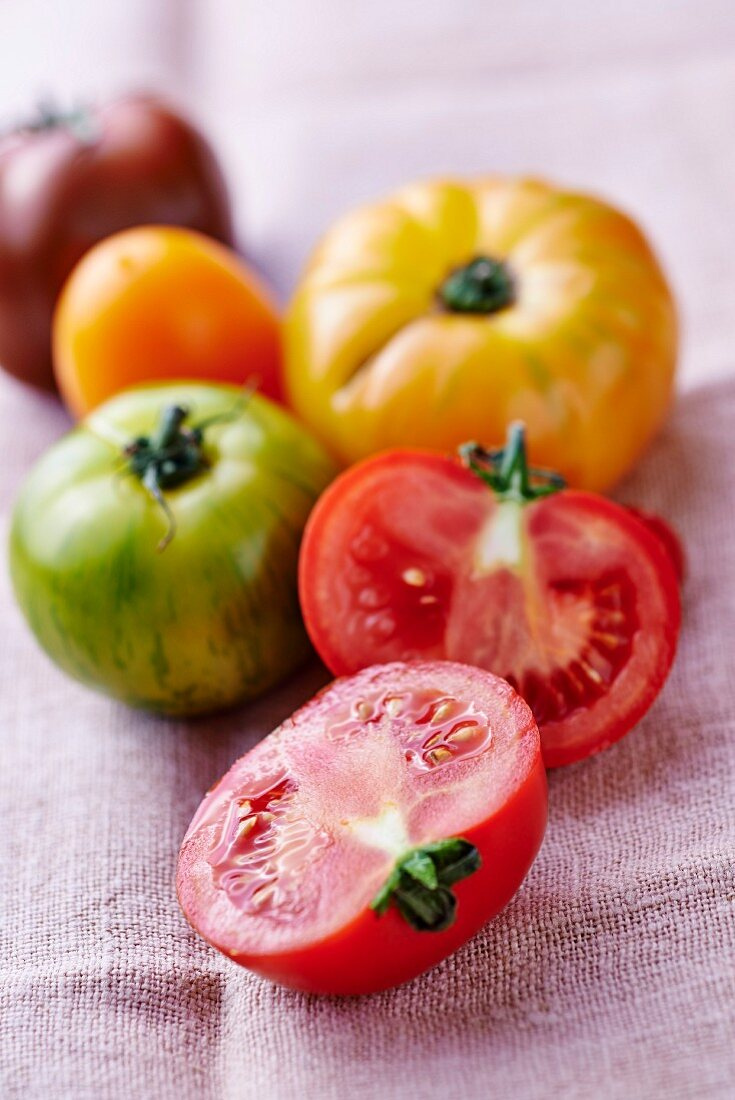 Various coloured tomatoes on a linen cloth, one halved