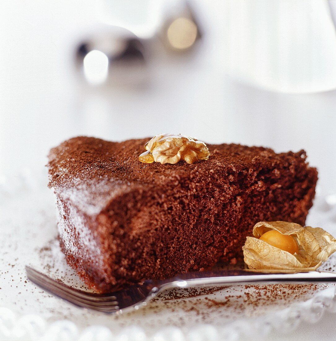 A piece of chocolate cake with nuts, honey and physalis