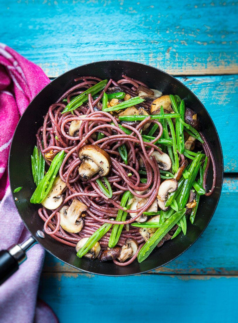 Pasta in red wine sauce with mushrooms, walnuts and peas