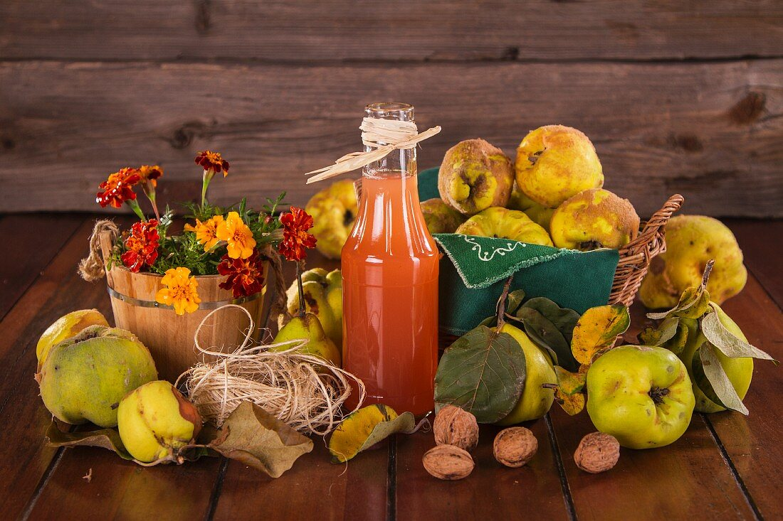 Still life with quinces, quince juice, walnuts and flowers