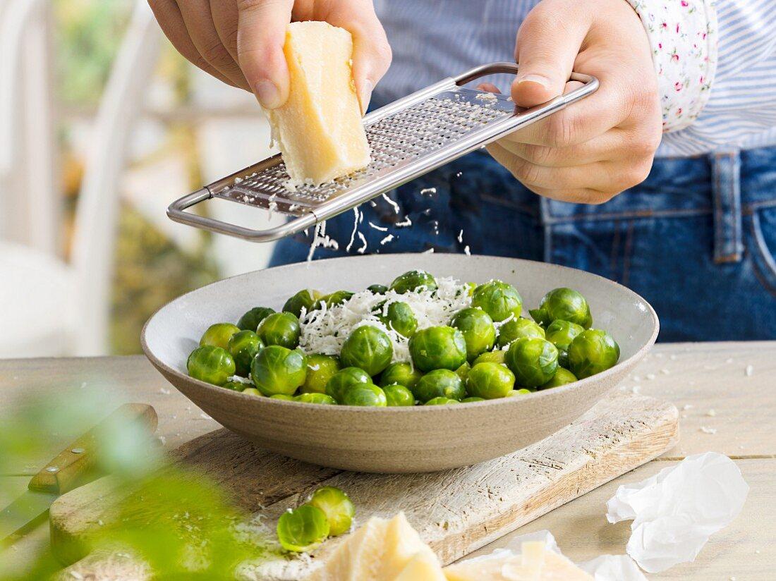 Mann reibt Käse über Rosenkohl